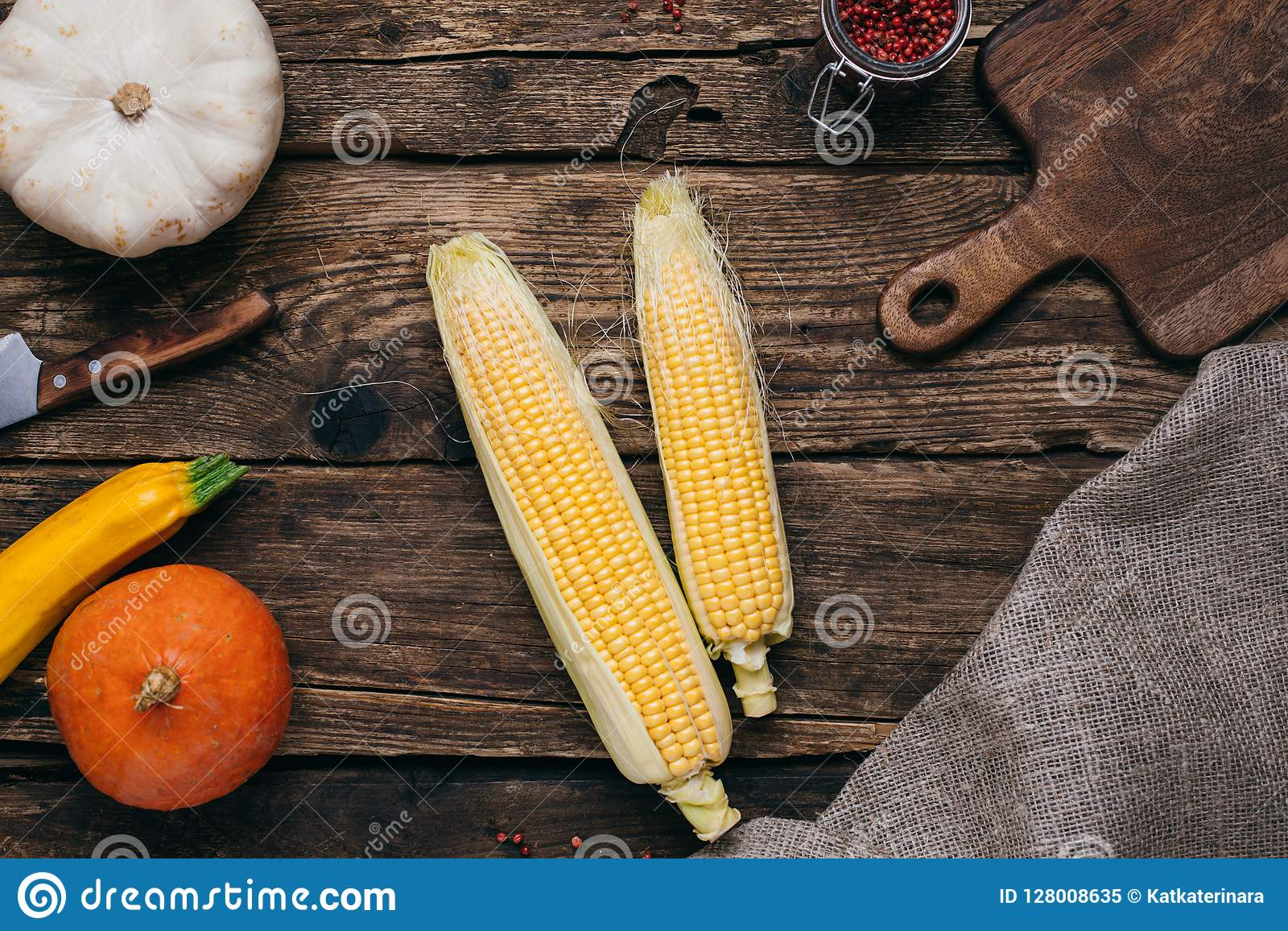 Verduras del otoño: calabazas y maíz con las hojas del amarillo y tablero cortado en un fondo de madera