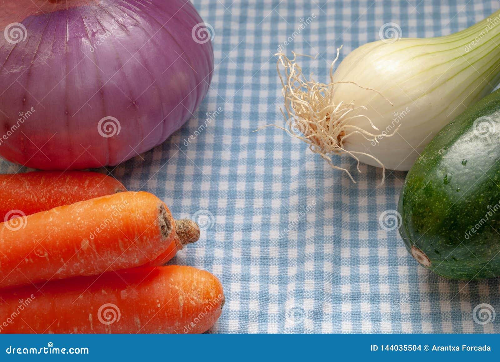 Verduras en el paño a cuadros azul y blanco de la cocina