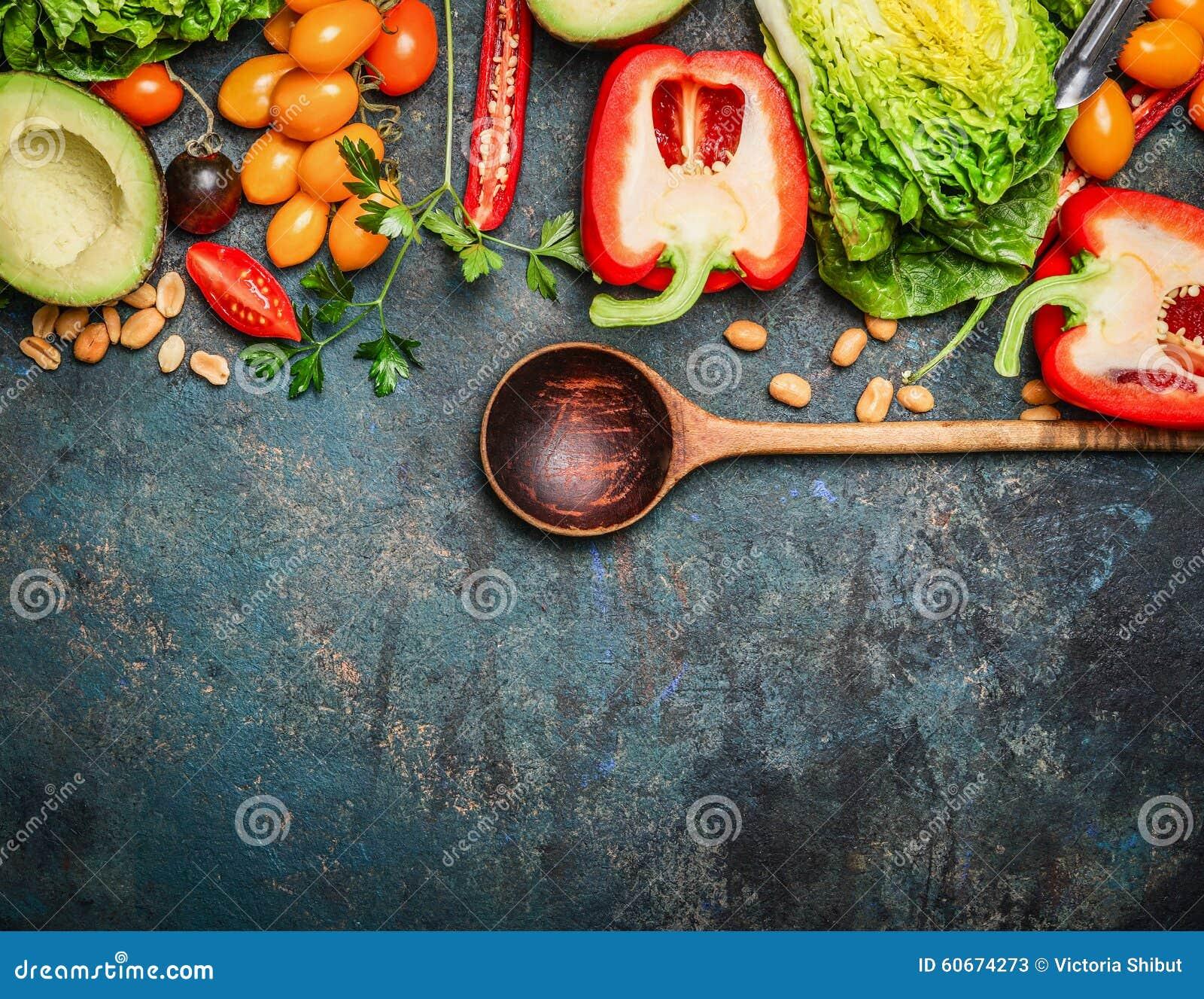 Verduras orgánicas coloridas con la cuchara de madera, los ingredientes para la ensalada o el relleno en el fondo de madera rústi