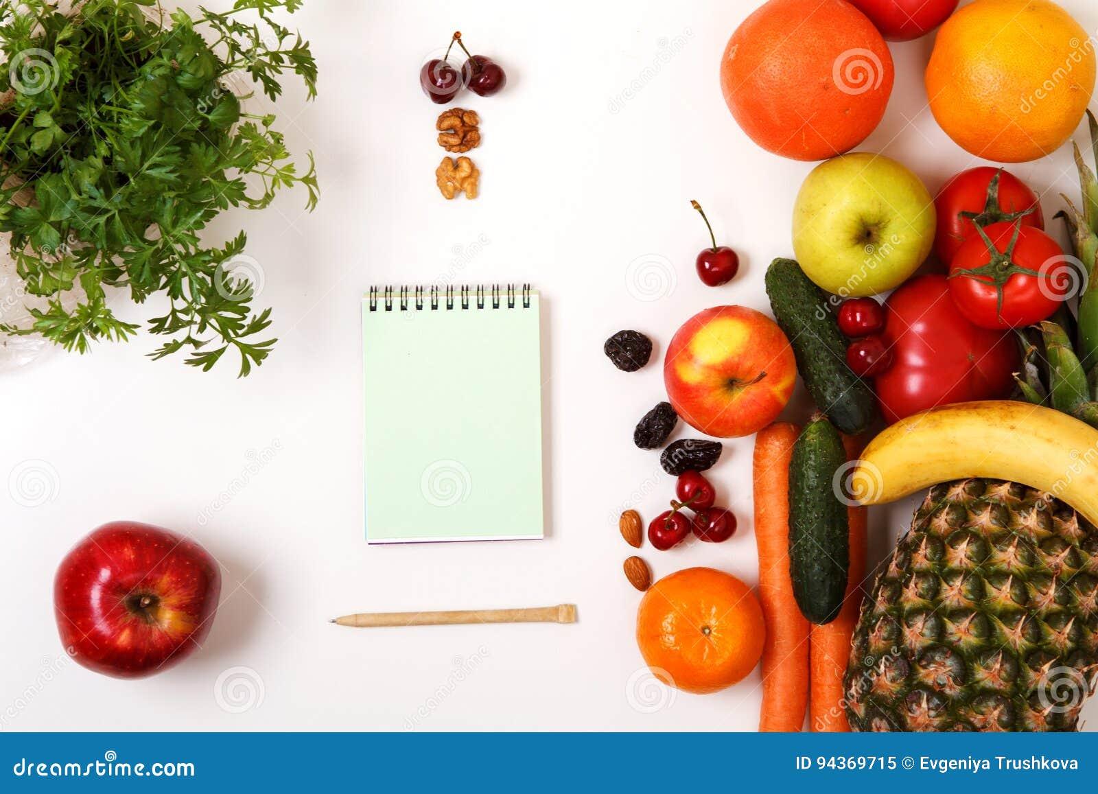 Verduras y frutas orgánicas frescas, cuaderno en blanco abierto