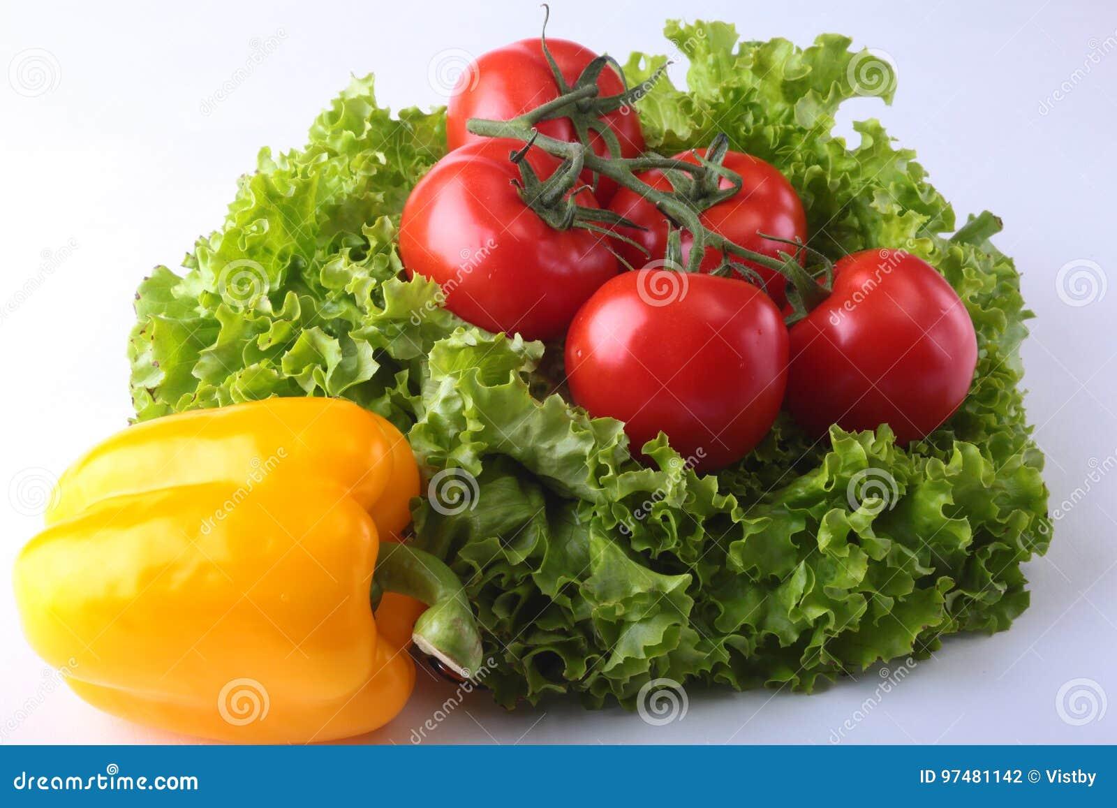 Verdure assortite fresche peperone dolce, pomodoro, aglio con la lattuga di foglia Su fondo bianco Fuoco selettivo
