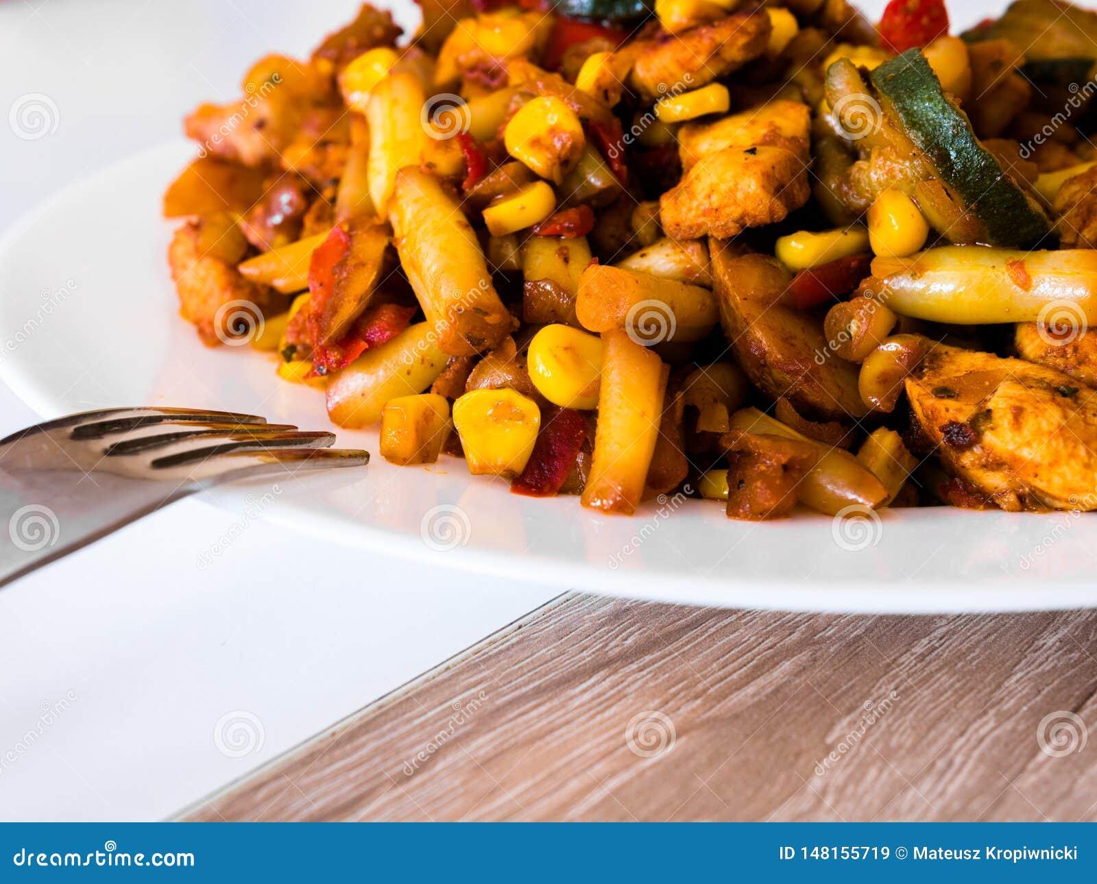 Verdure con pollo fritto sul piatto bianco