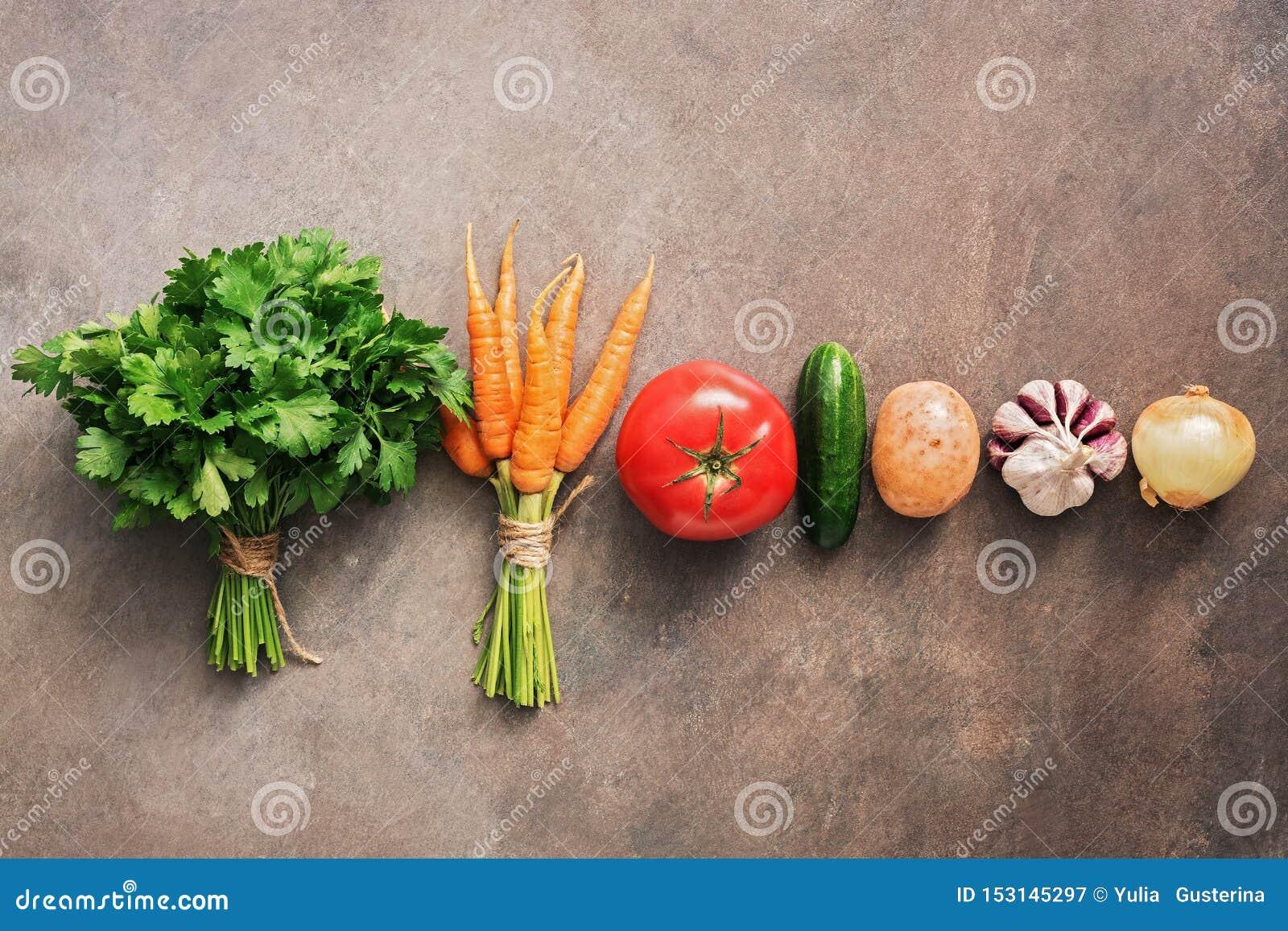 Verdure crude fresche in una fila su un fondo rustico scuro Il concetto di cibo sano Il nuovo raccolto delle verdure Vista superi