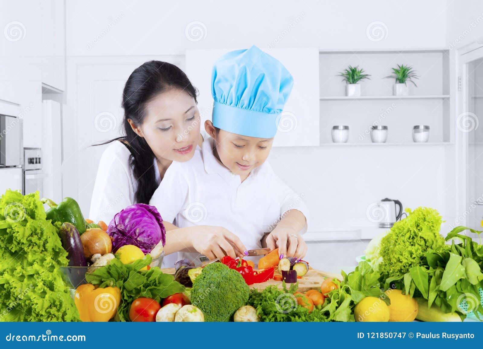 Verdure di taglio del bambino con sua madre