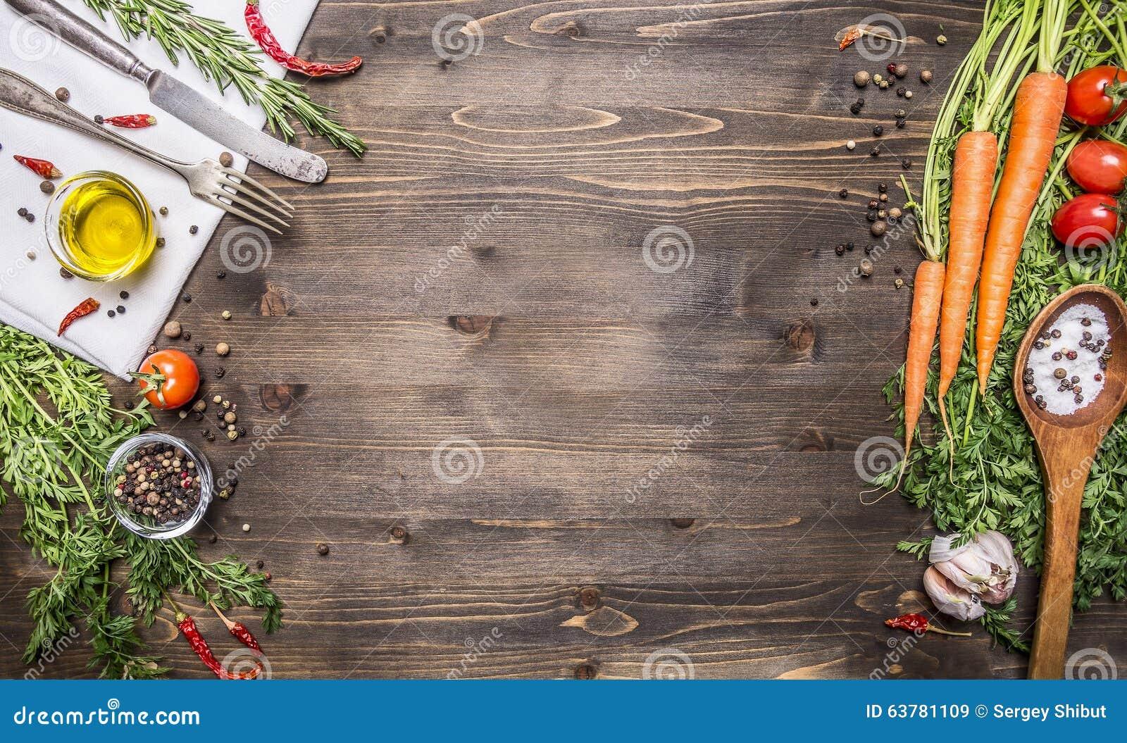 Verdure e cucchiai organici freschi su fondo di legno rustico, vista superiore, confine Alimento sano o concetto di cottura veget