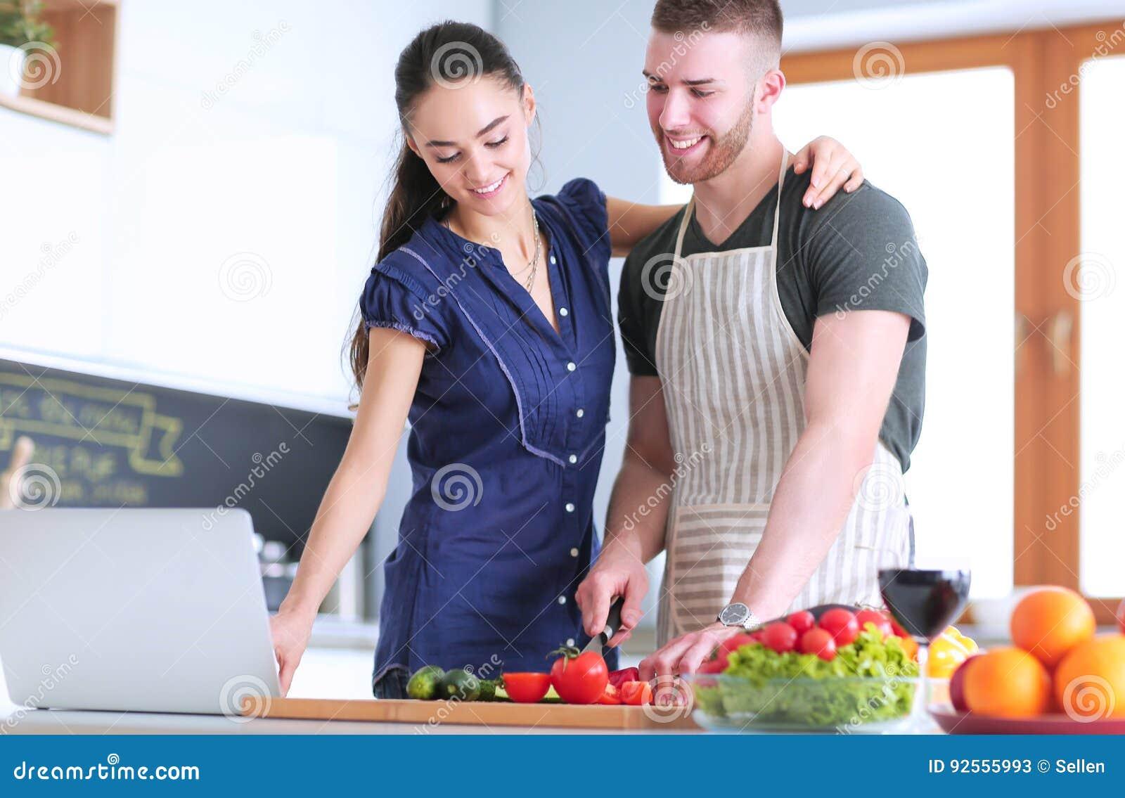 Verdure e donna di taglio del giovane che stanno con il computer portatile nella cucina