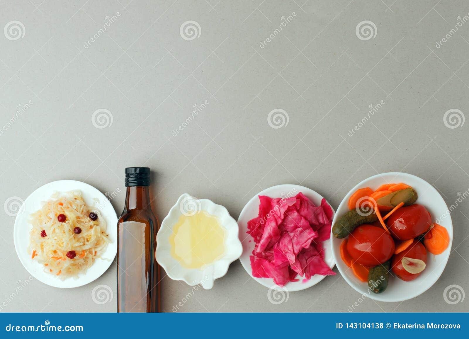 Verdure fermentate sul piatto su fondo grigio: crauti, cavolo marinato con barbabietola, cetrioli marinati, carote e
