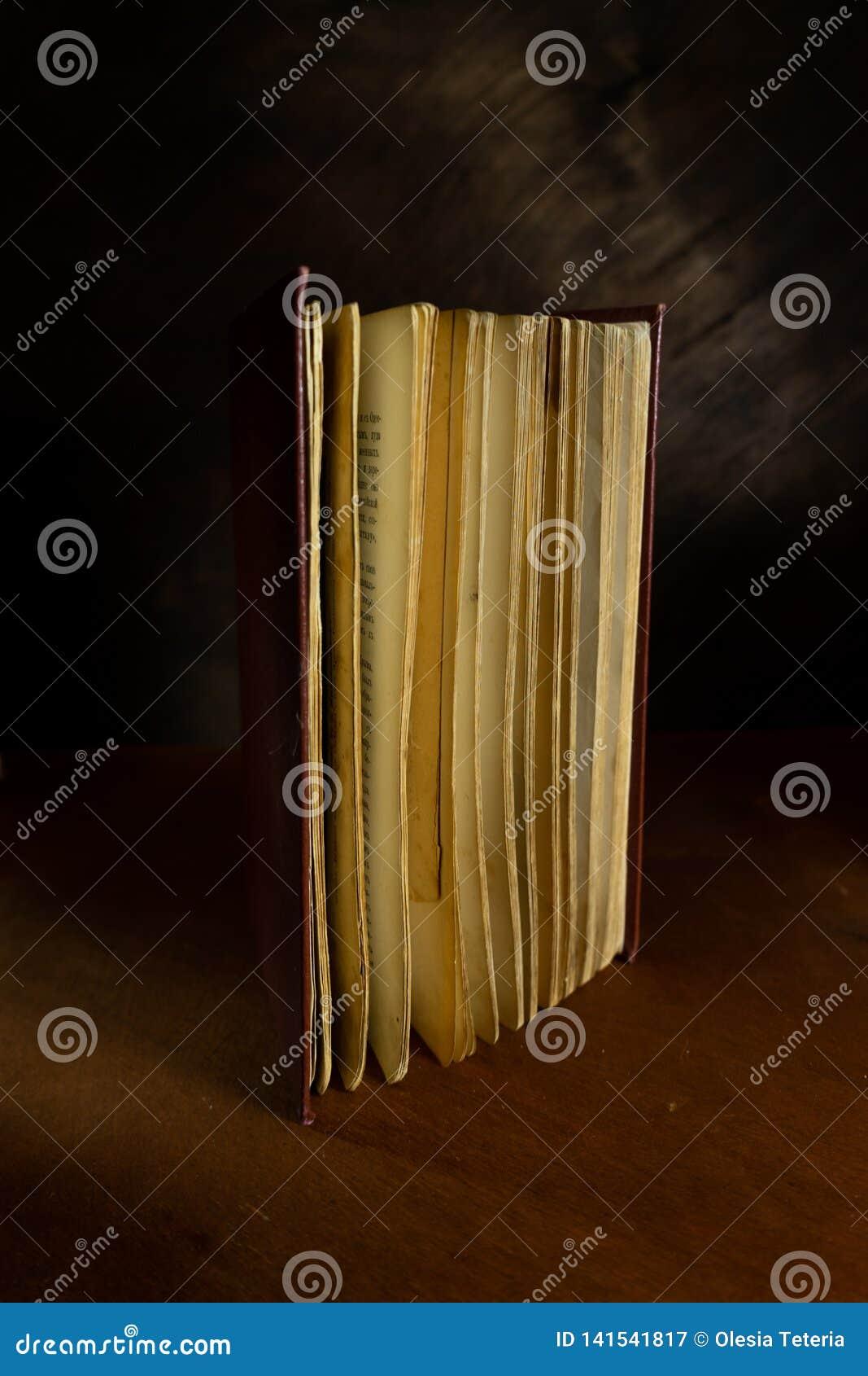 Verfallenes altes Buch in der aufrechten Position auf hölzernem dunklem Hintergrund