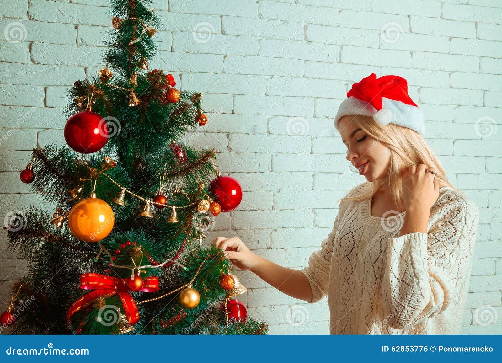 Verfraait het pret jonge blonde een Kerstmisboom in santahoed