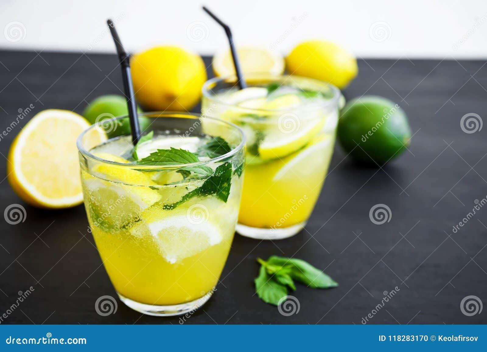 Verfrissende limonade in glas met kalk, citroenen en munt De zomerdranken