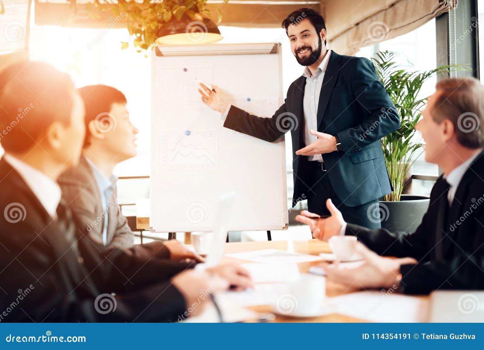 Vergadering met Chinese zakenlieden in bureau De mens toont raad met grafieken en grafieken