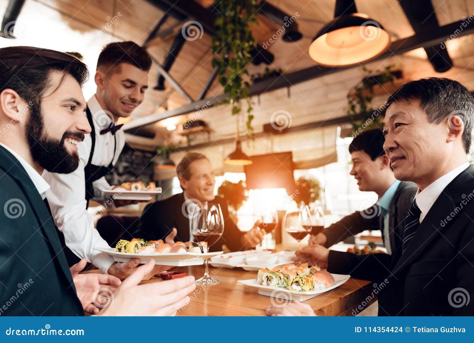 Vergadering met Chinese zakenlieden in restaurant De kelner brengt sushi