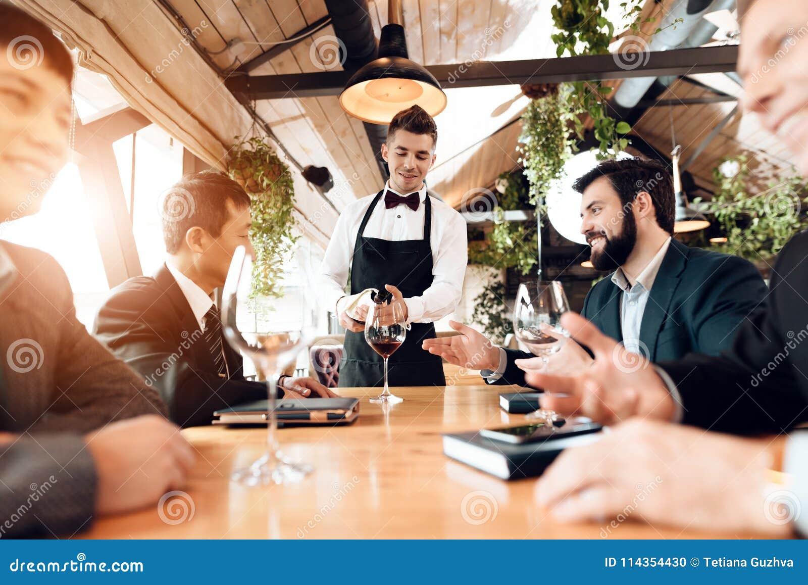 Vergadering met Chinese zakenlieden in restaurant De kelner giet wijn in glazen