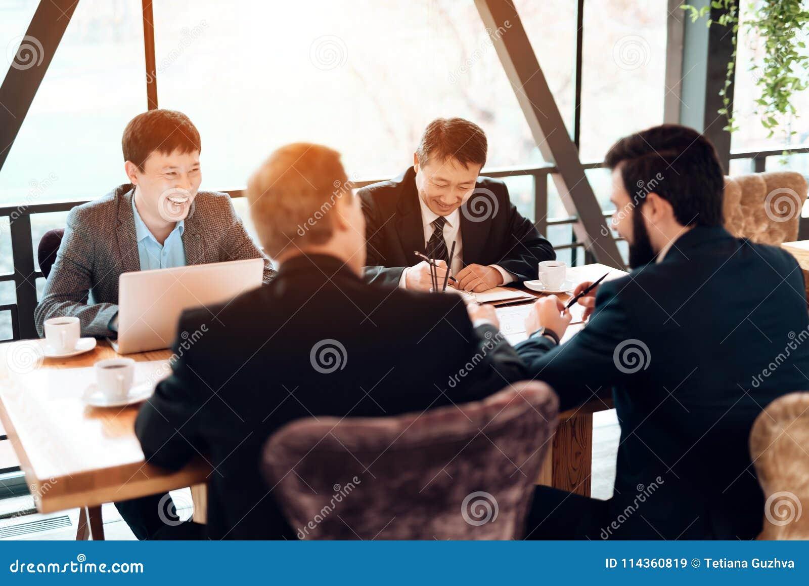 Vergadering met Chinese zakenlieden in restaurant De mensen laughting