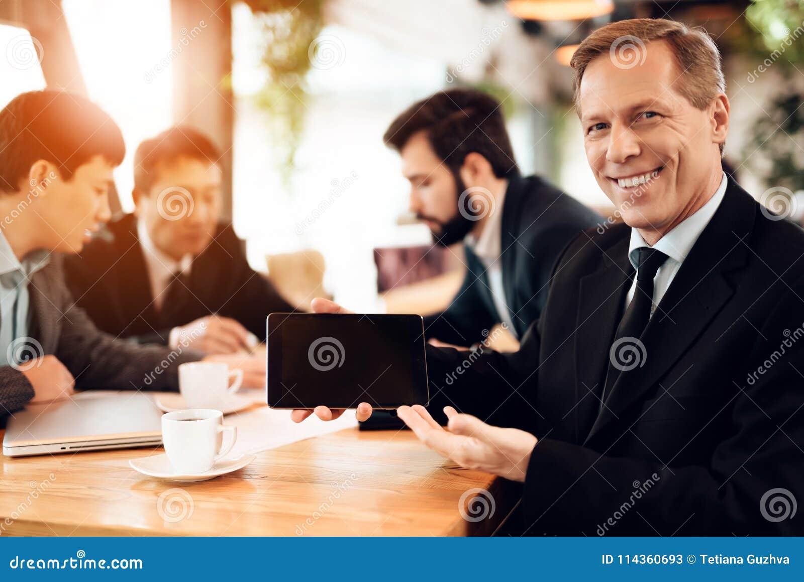 Vergadering met Chinese zakenlieden in restaurant Mens die tablet tonen bij camera