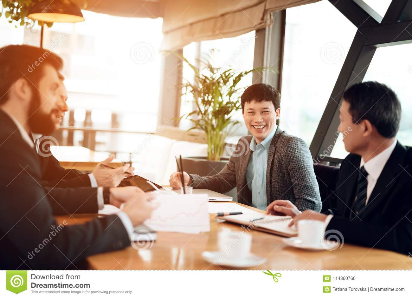 Vergadering met Chinese zakenlieden in restaurant Zij bespreken punt in documenten