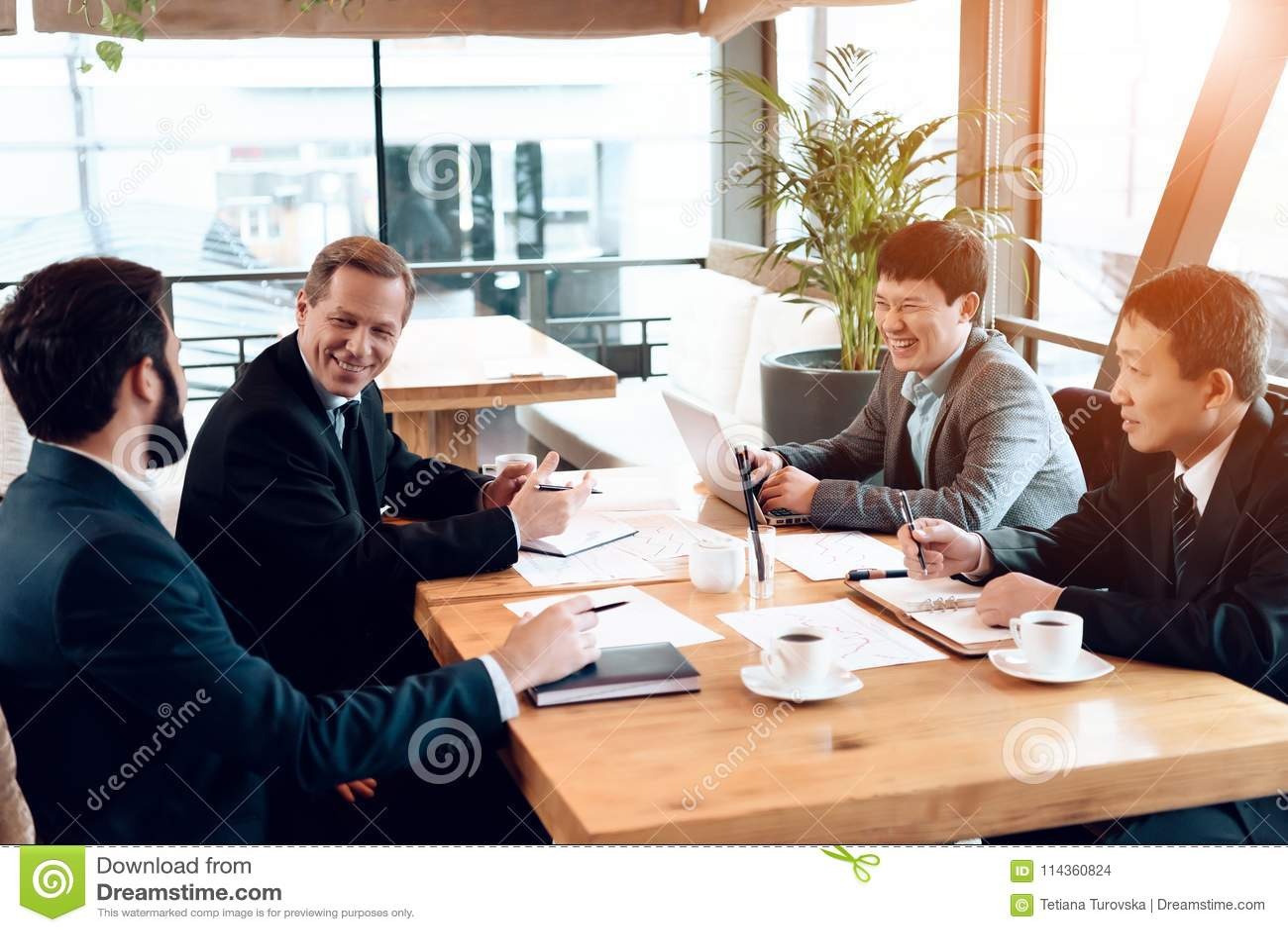 Vergadering met Chinese zakenlieden in restaurant Zij zitten achter lijst