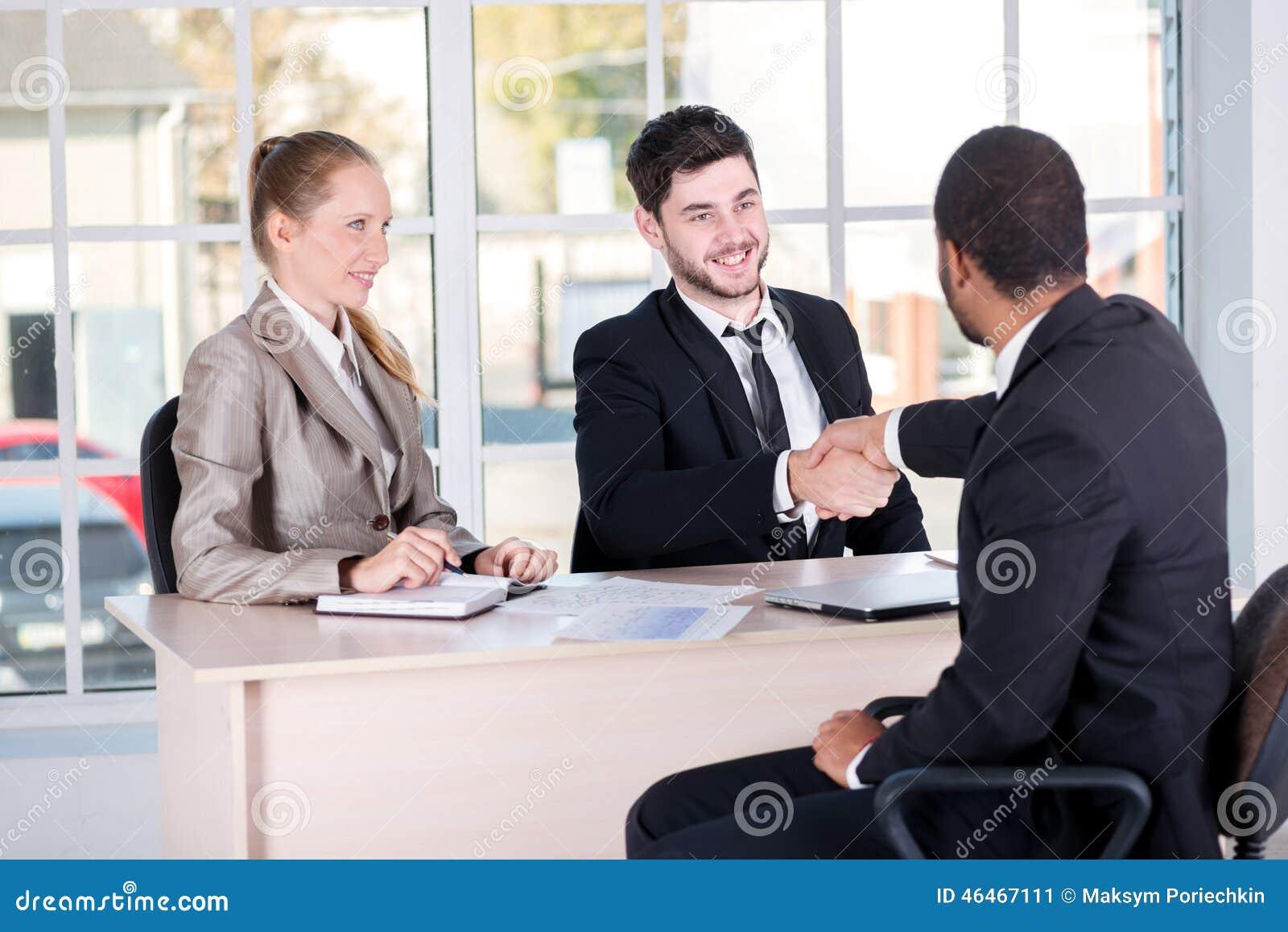 Vergadering van partners Drie succesvolle bedrijfsmensen die aanwezig zijn