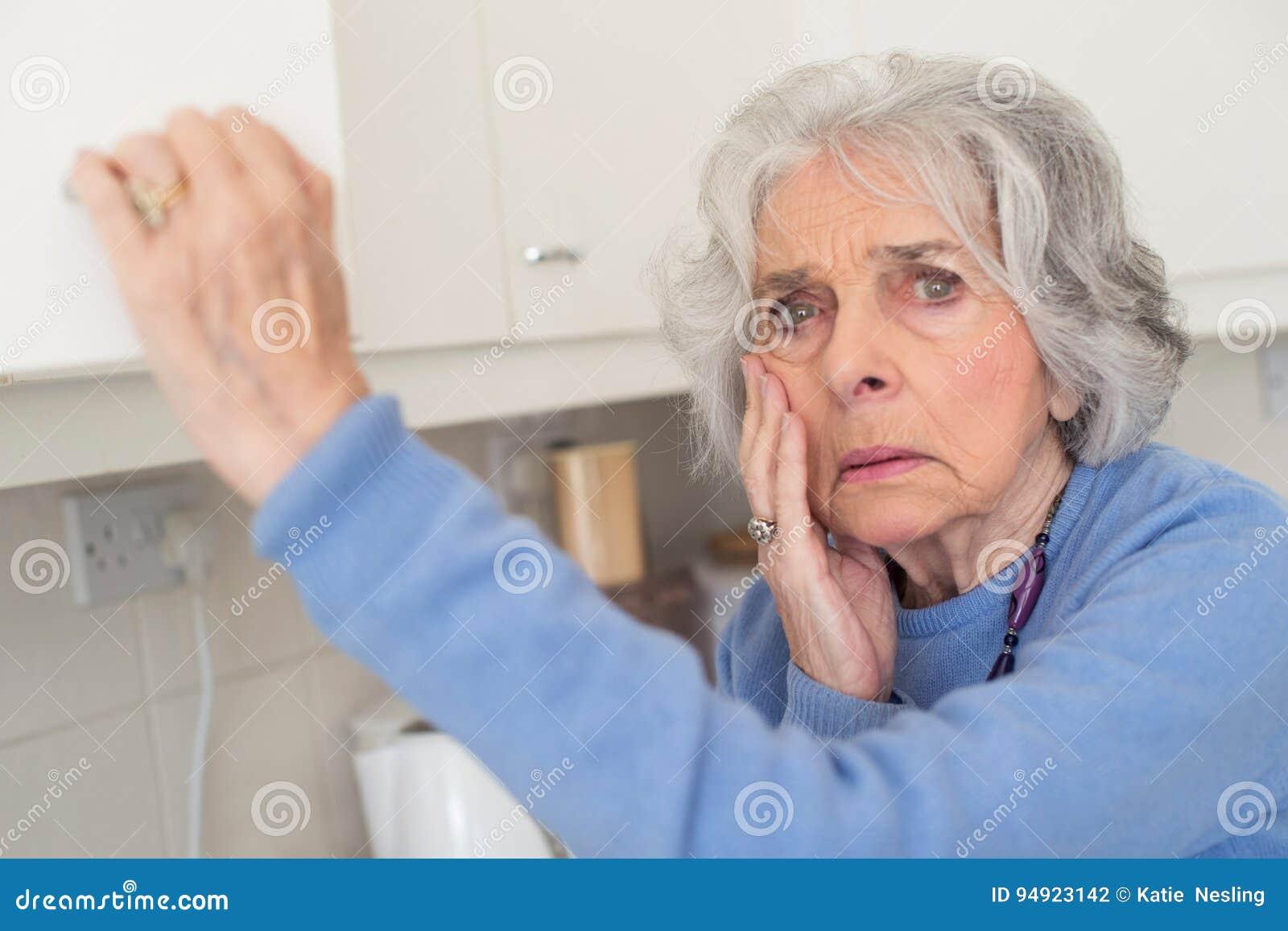 Vergessliche ältere Frau mit der Demenz, die im Schrank schaut