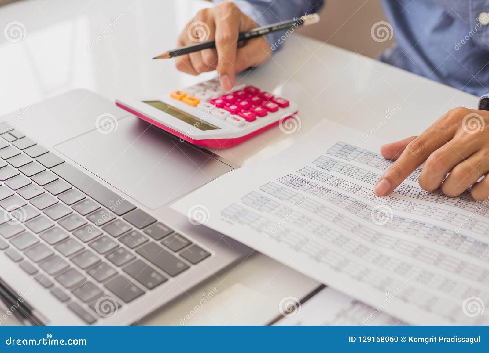 Verificação do homem de negócios sobre o custo e fazer dados do relatório da finança