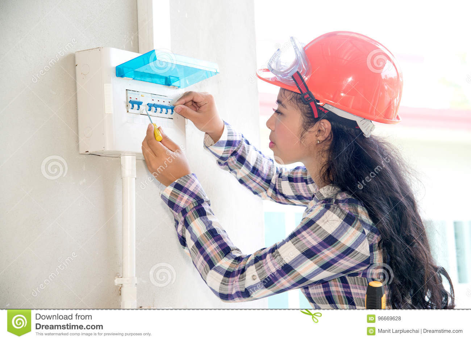 A verificação fêmea asiática do eletricista ou do coordenador ou inspeciona o interruptor do sistema bonde