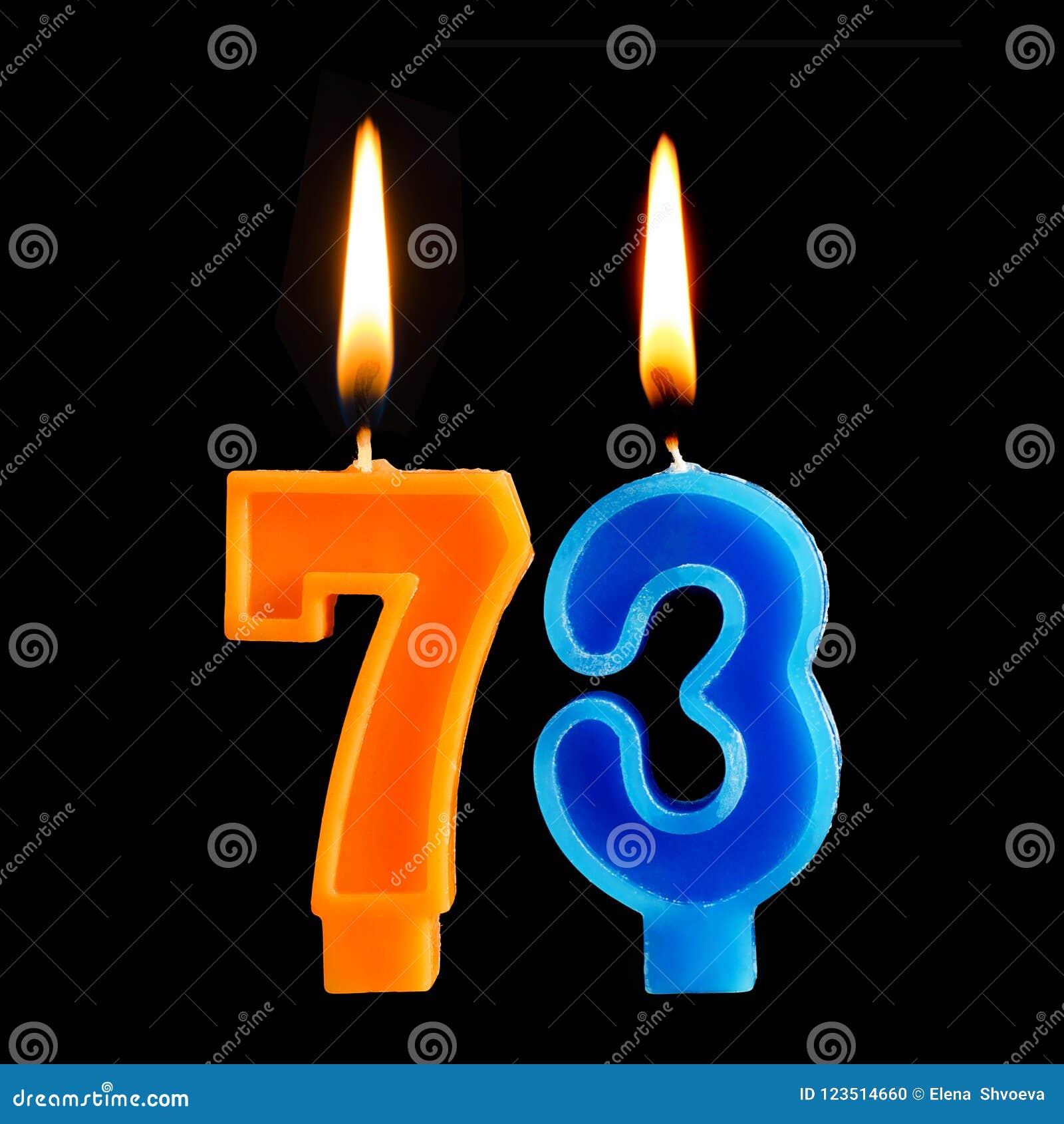Verjaardags brandende kaarsen in de vorm van 73 die drieënzeventig voor cake op zwarte achtergrond wordt geïsoleerd