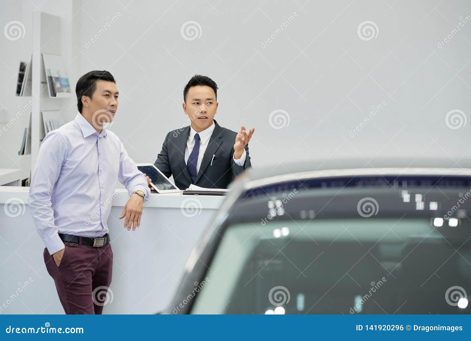 Verkäufer, der dem Kunden Autos zeigt