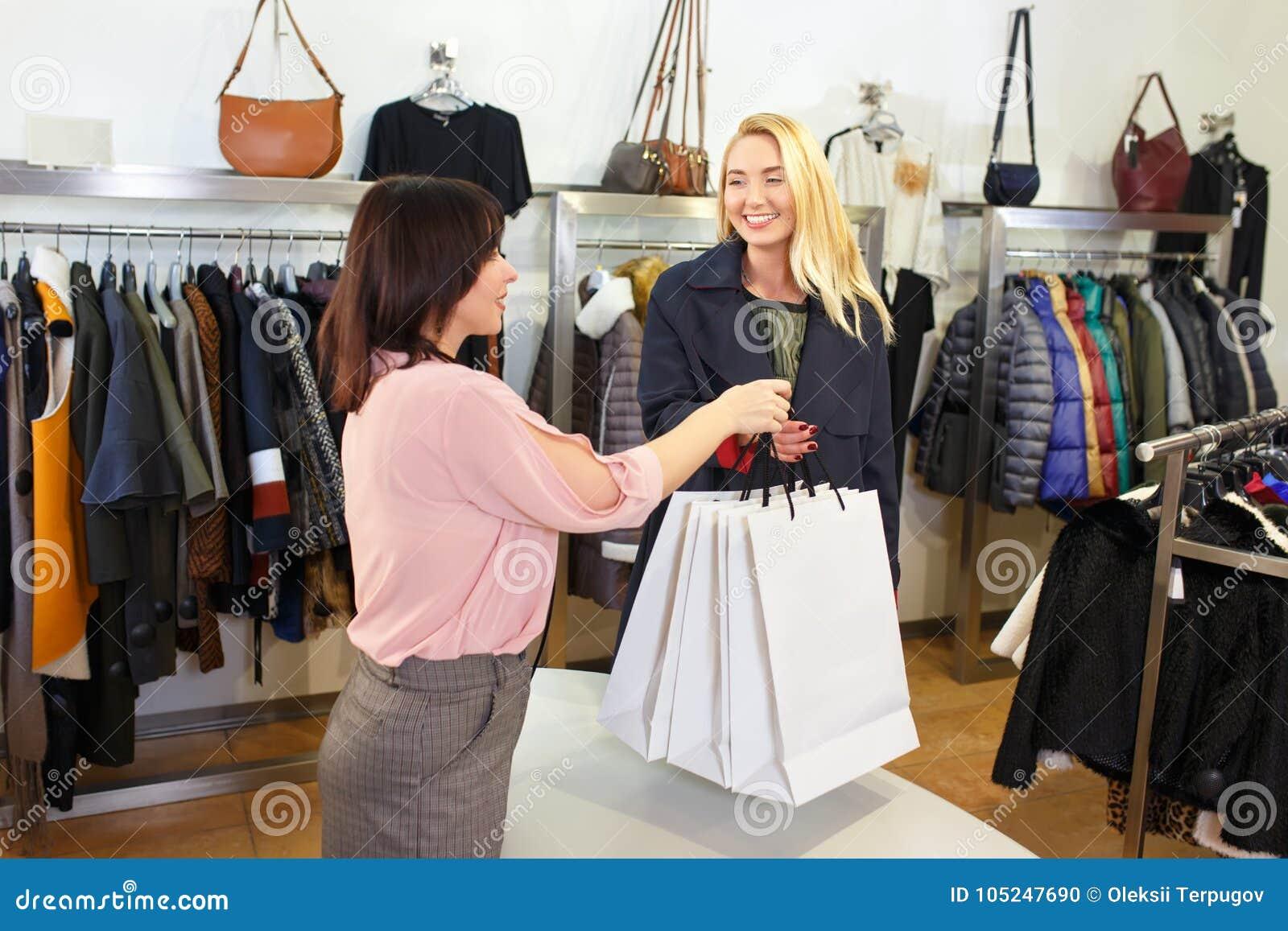Verkäufer, der Einkaufstaschen für Kunden gibt