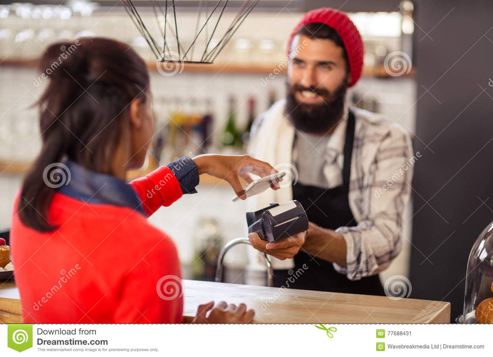 Verkäufer, der Zahlung mit Bankkarte Leser und Smartphone nimmt