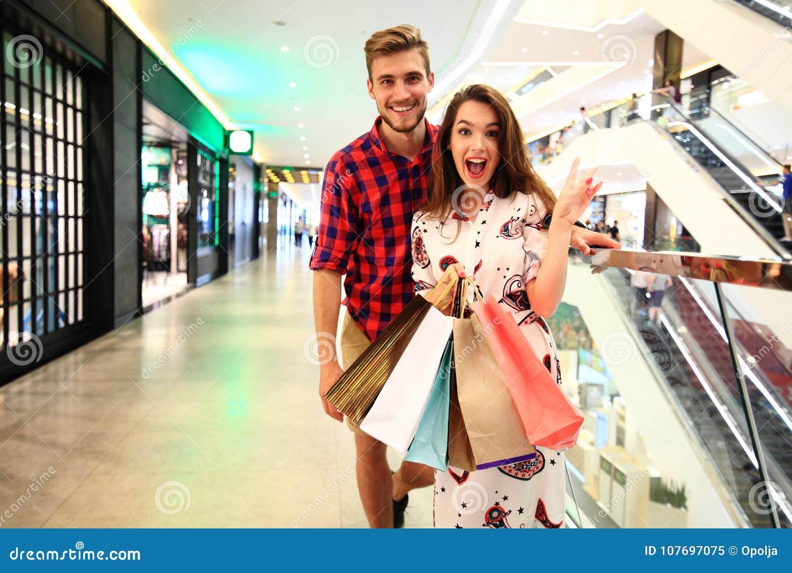 Verkauf, Verbraucherschutzbewegung und Leutekonzept - glückliches junges Paar mit den Einkaufstaschen, die in Mall gehen