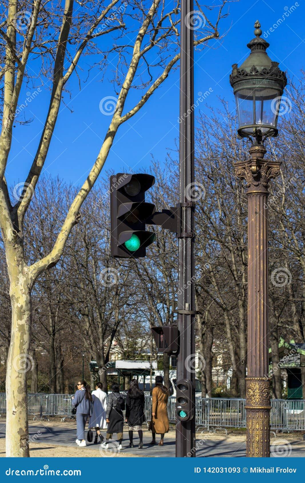 Verkeerslicht, lantaarn, boom tegen de blauwe hemel in de lente in Parijs, waar de mensen in goed weer lopen
