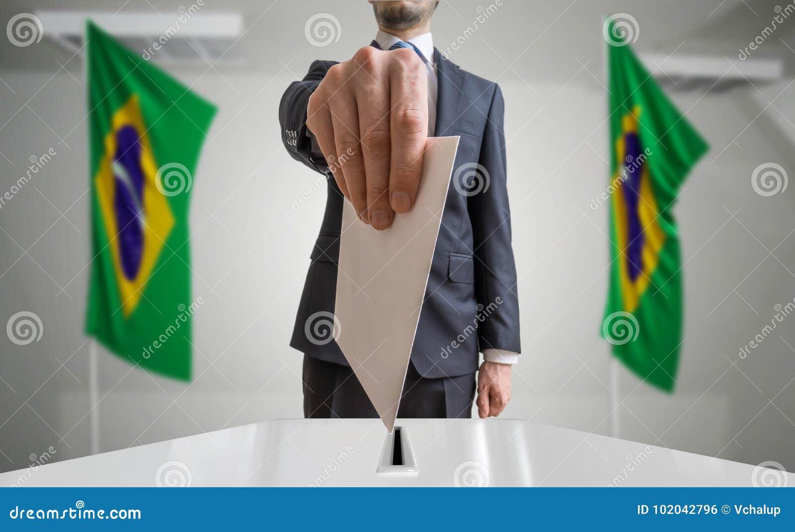 Verkiezing of referendum in Brazilië De kiezer houdt envelop boven stemming in hand Braziliaanse vlaggen op achtergrond