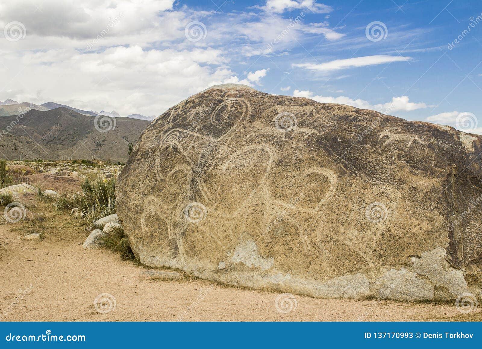 Verkliga petroglyphs på den naturliga stenen som finnas i stäppen, på en suddig bakgrund av härliga berg