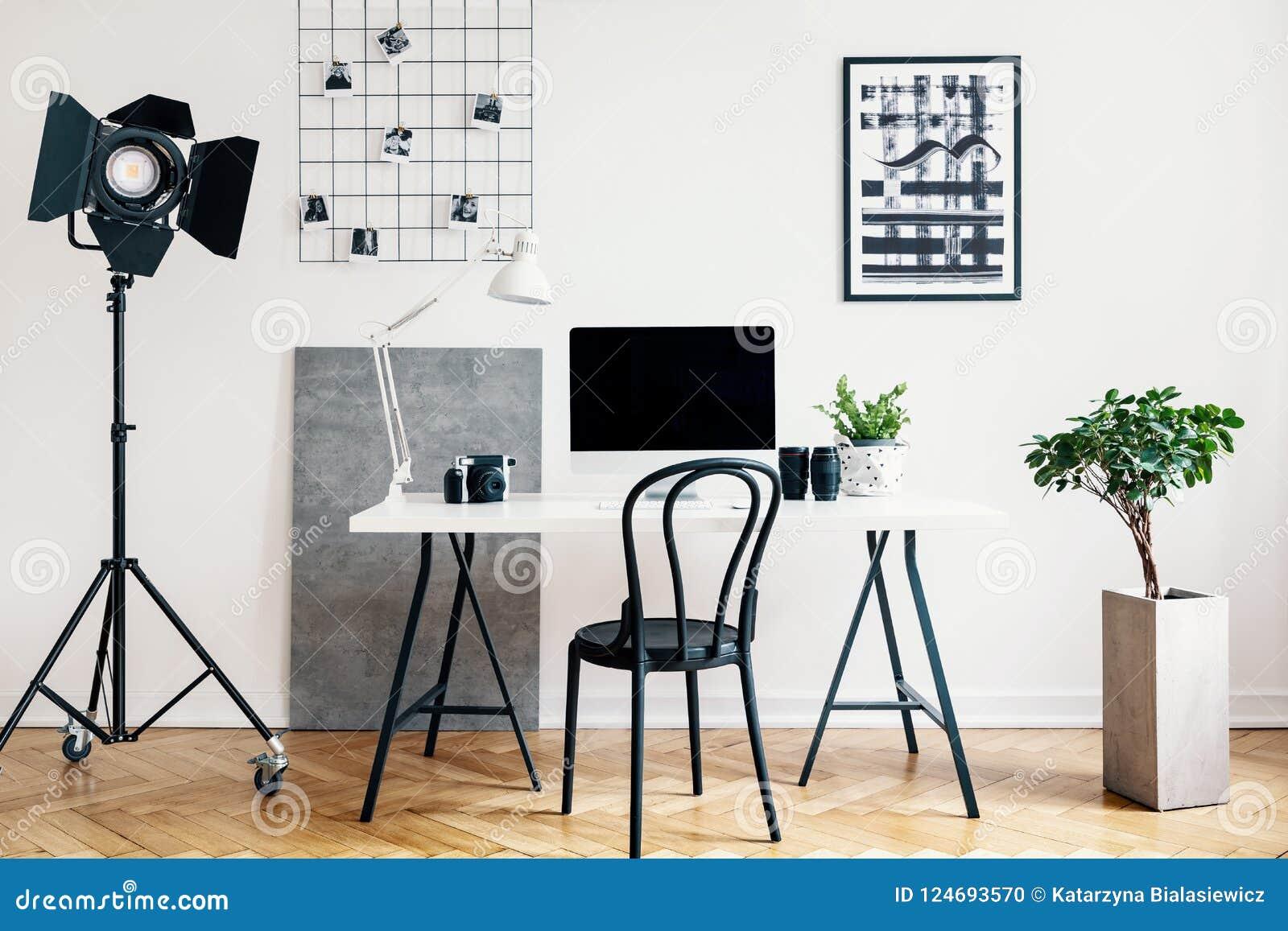 Verkligt foto av en inrikesdepartementetinre med en yrkesmässig lampa, skrivbord, stol, dator och växt Förlägga din logo på dator
