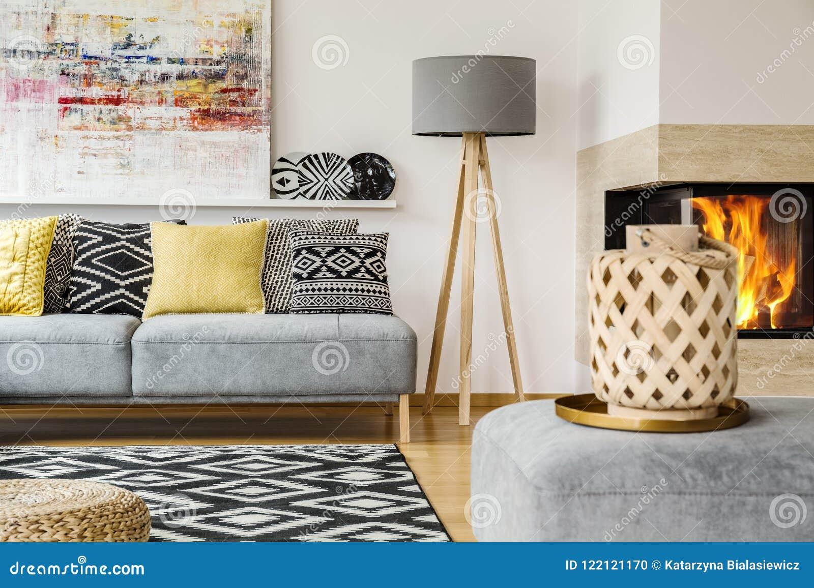 Verkligt foto av en soffa med kuddar som står bredvid en lampa och ett b