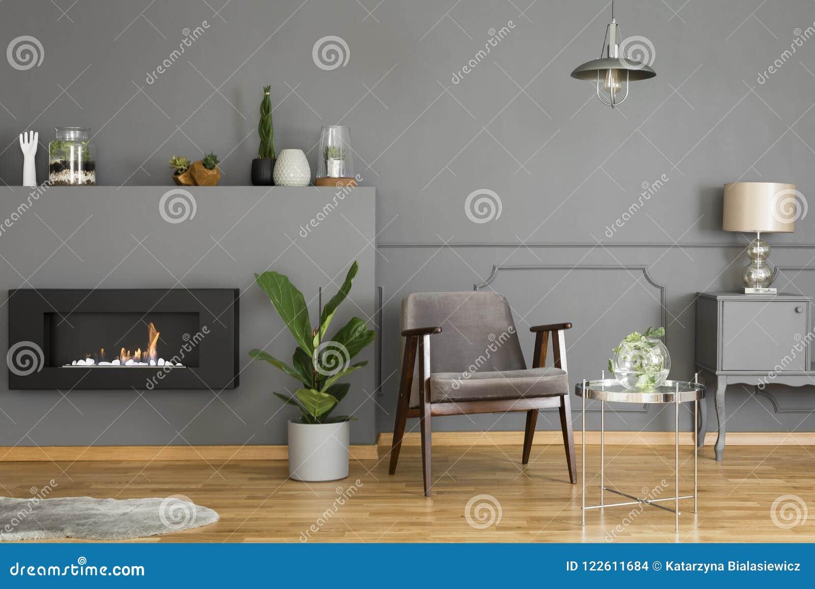 Verkligt foto av ett grått fåtöljanseende i en modern enkel livin