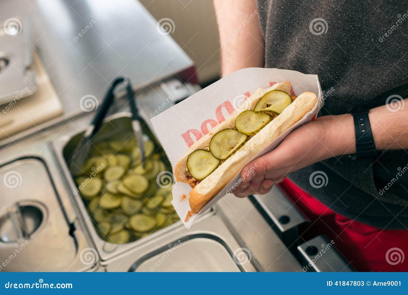 Verkoper die hotdog in snel voedselsnackbar maken
