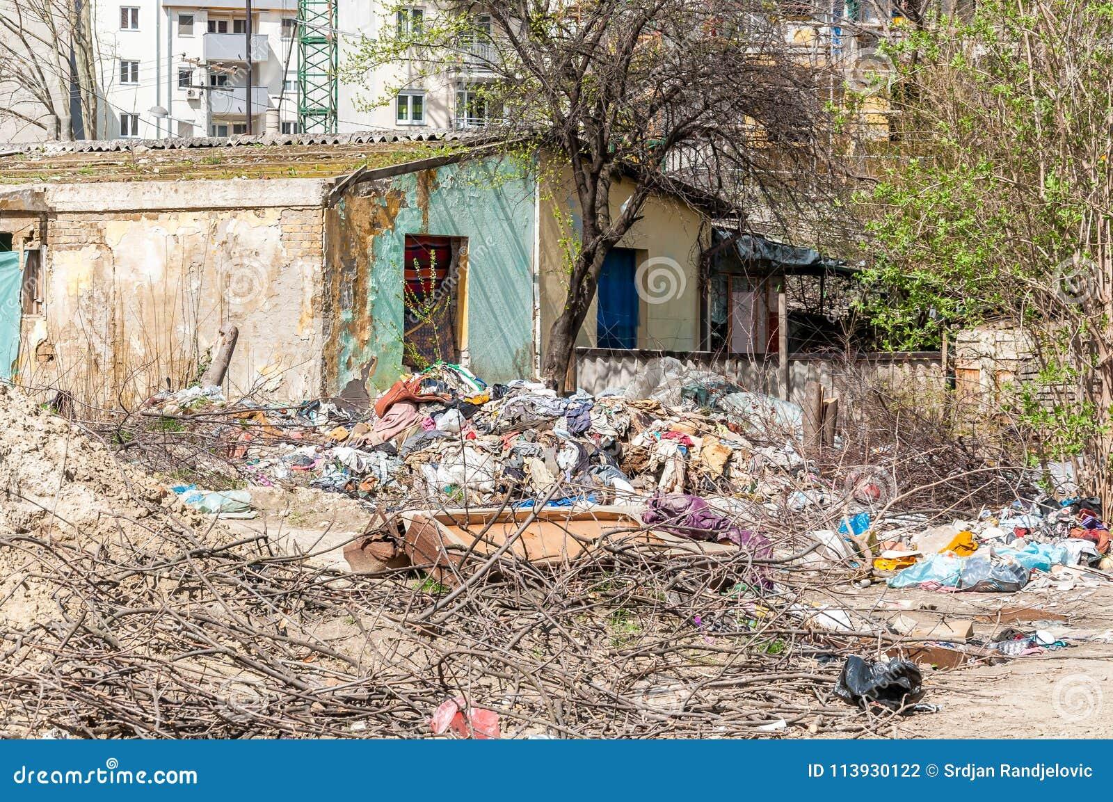 Verlassenes ländliches schädigendes Haus im Getto nahe neuem Wohngebäude in der Stadt benutzt als Müllkippe mit Kram und Sänfte h