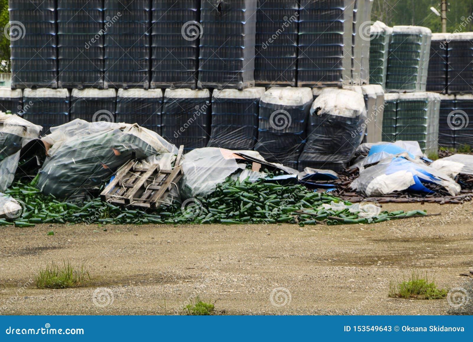 Verlaten glasfabriek ingepakte flessen in pallets, gebroken flessen op asfalt, veel losse flessen en huisvuil van productie