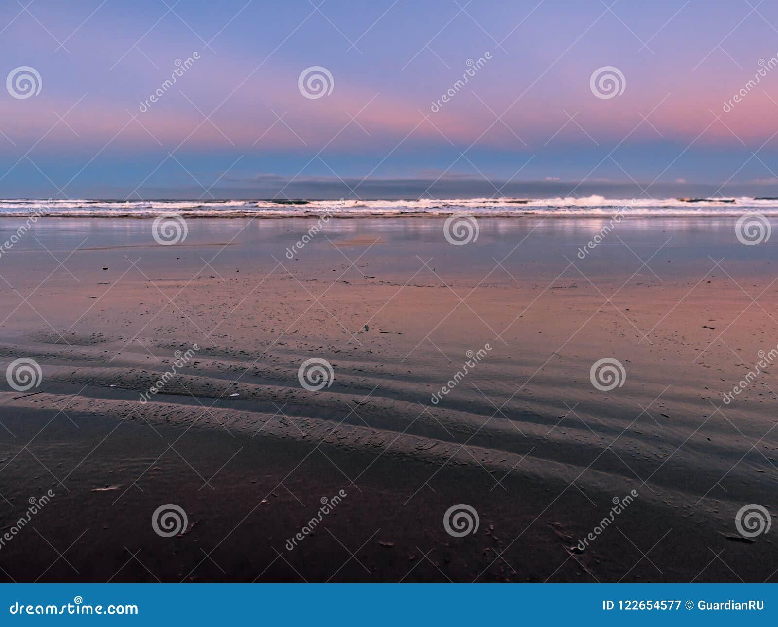 Verlaten oceaanstrand bij dageraad