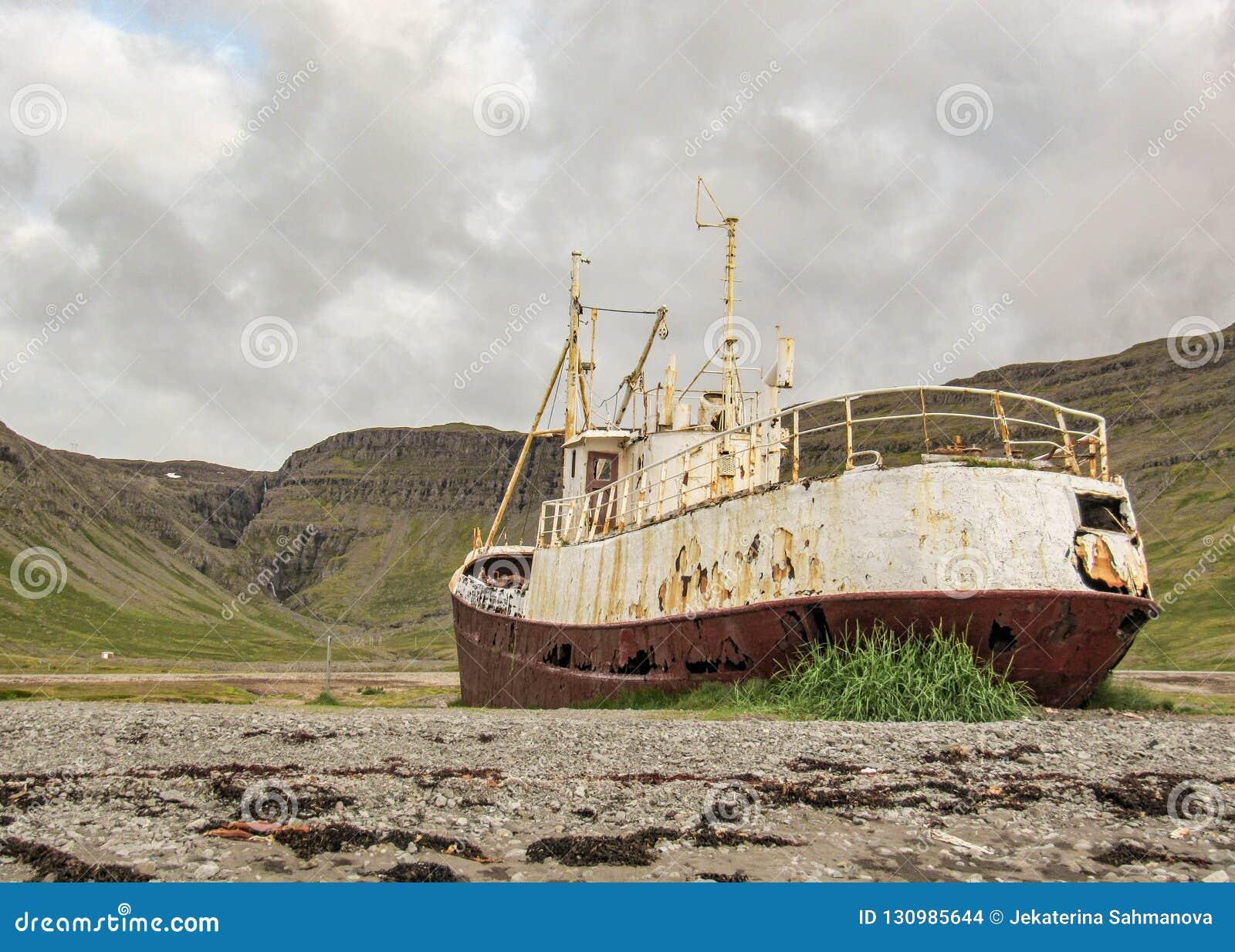 Verlaten reusachtige geroosterde staalboot in Westfjords, IJsland