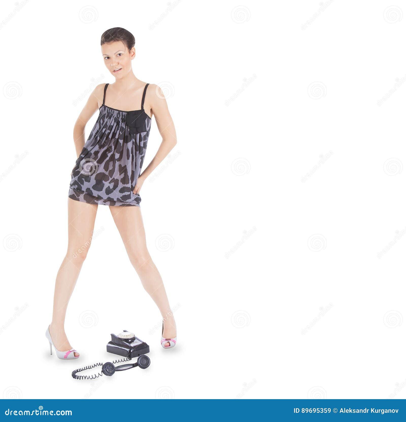 Verleidelijk meisje in kleding die zich over de uitstekende telefoon bevinden