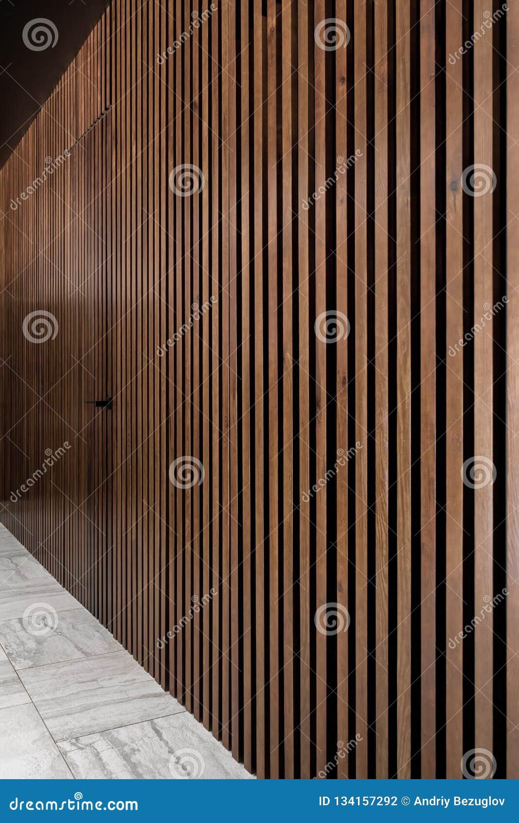 Verlicht binnenland met rooster houten muur met deur