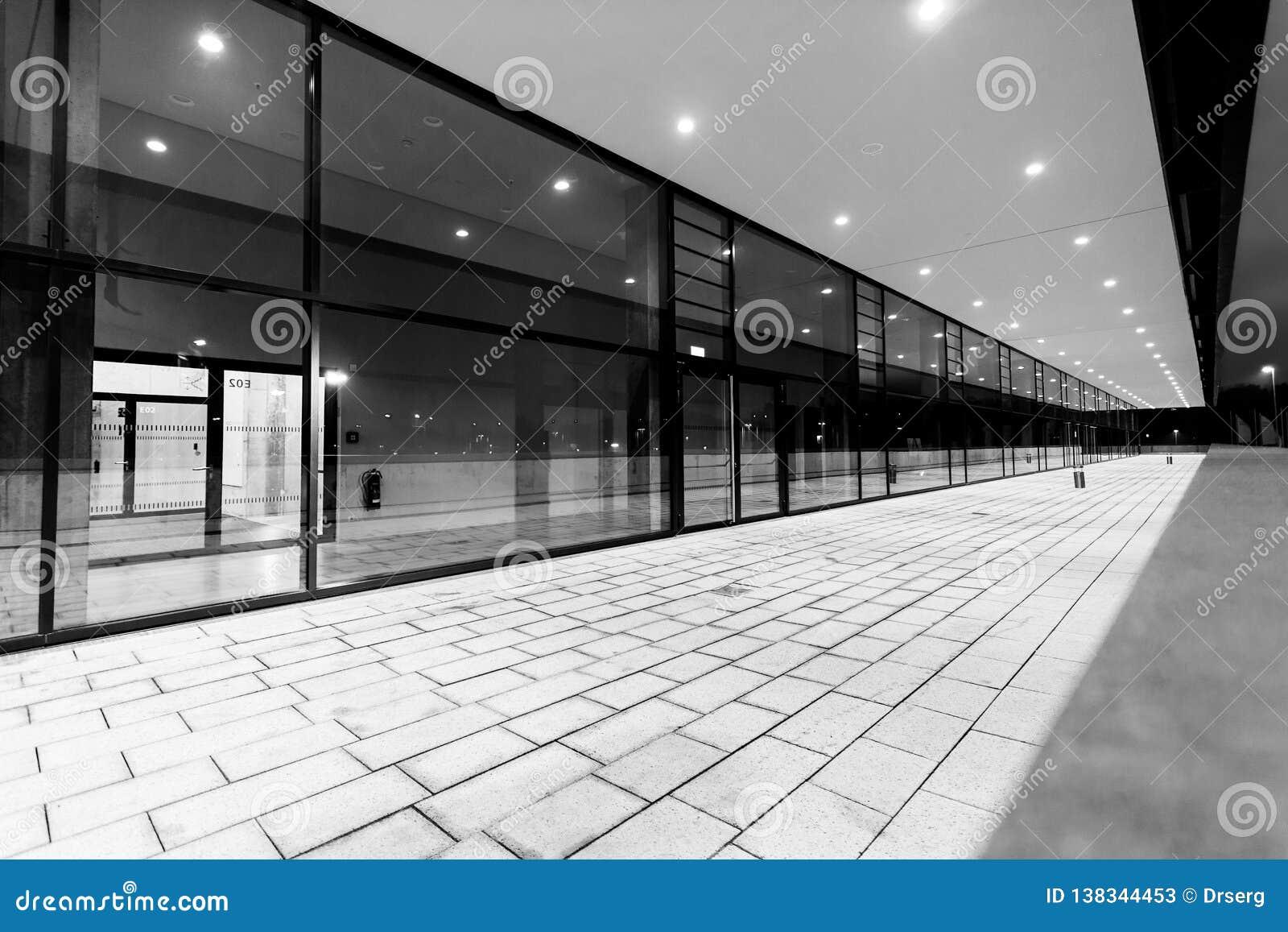 Verlicht voetpassageperspectief langs glas de bouwvoorgevel