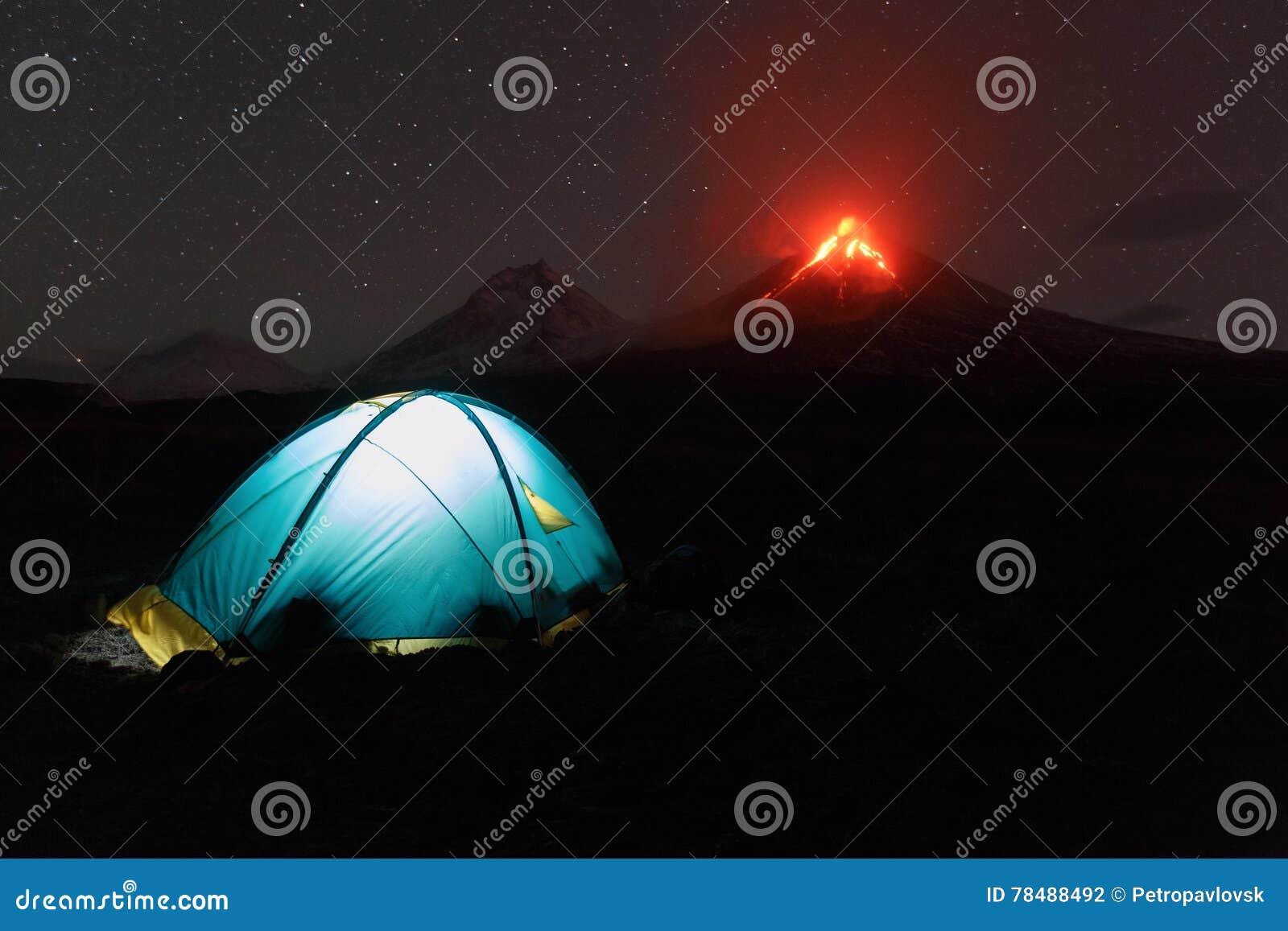 Verlichte toeristentent bij nacht op losbarstende vulkaan als achtergrond