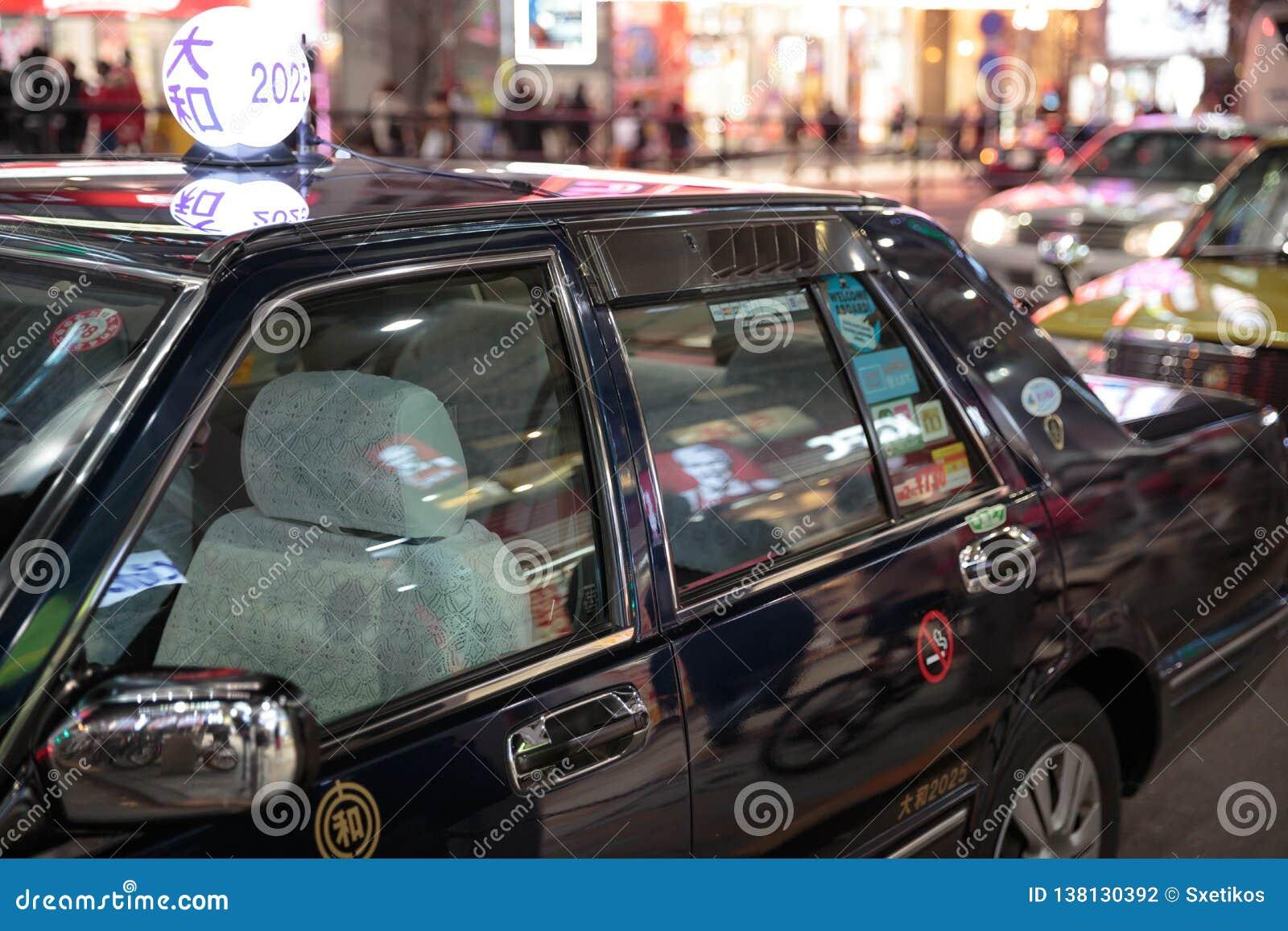 Verlichte zwarte taxi in straten van Tokyo