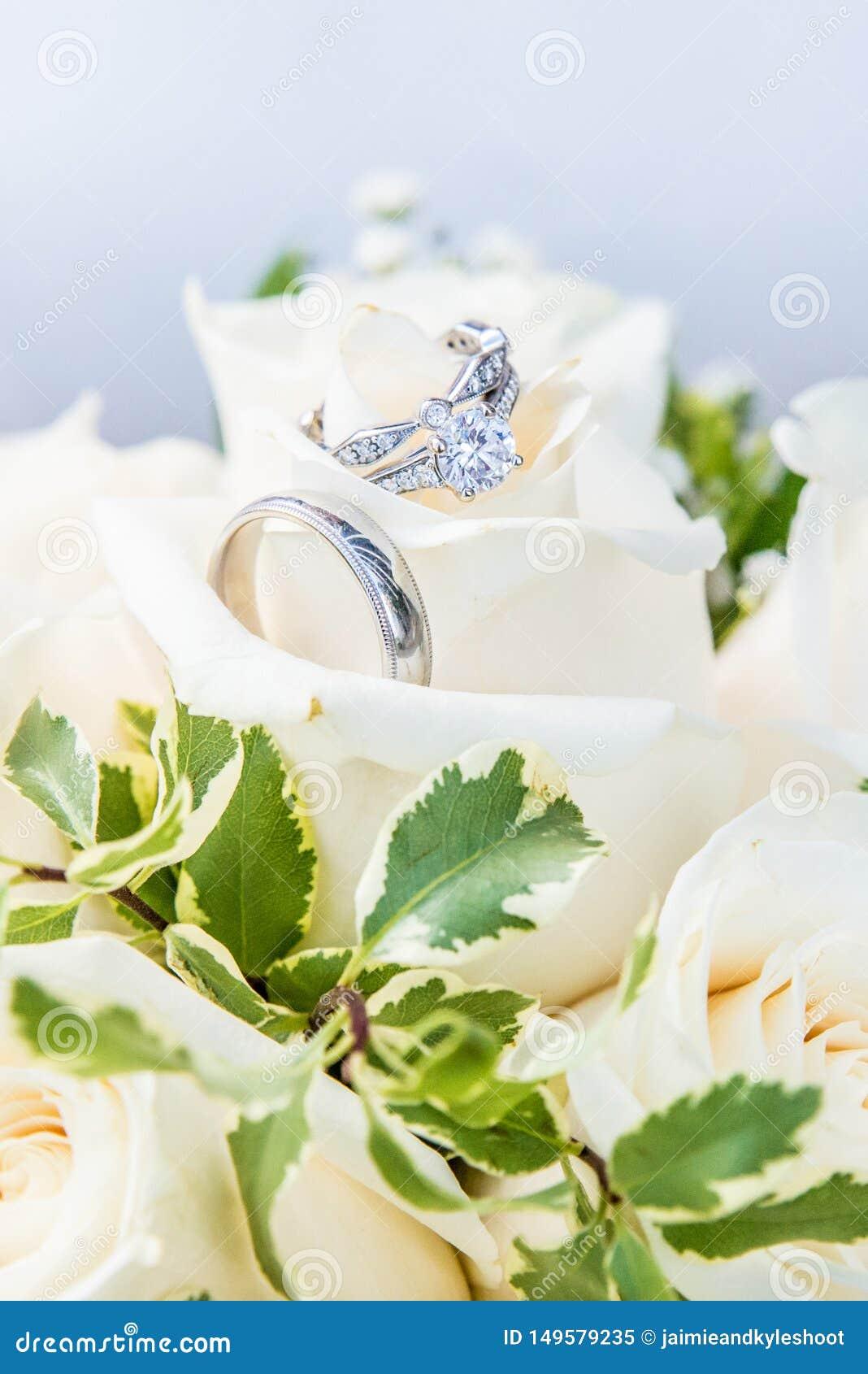 Verlobungsring zusammengepa?t mit den Hochzeitsb?ndern, stehend auf einem Blumenstrau? von wei?en Rosen still