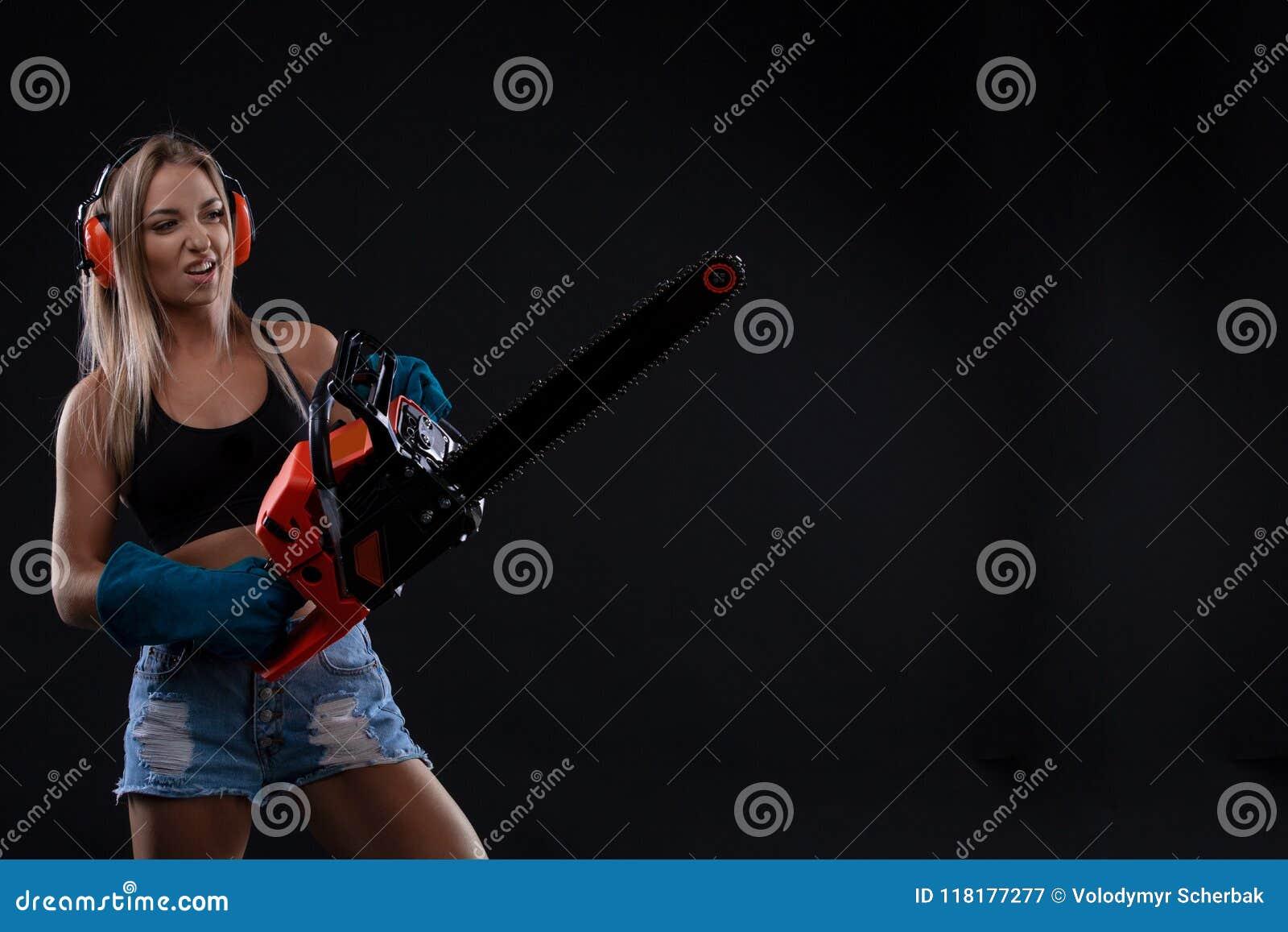 Verlockende junge Frau, die mit Kettensäge aufwirft