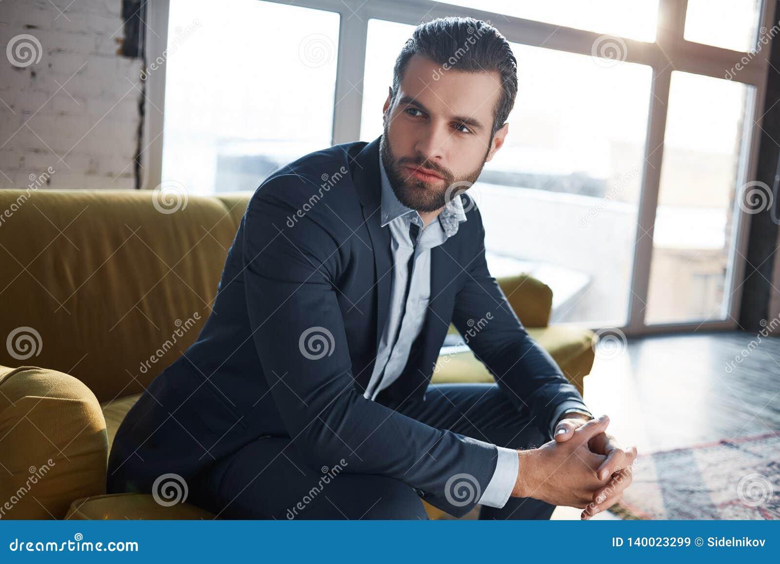 Verloren in bedrijfsgedachten De nadenkende knappe jonge zakenman denkt over zaken terwijl het zitten op de bank
