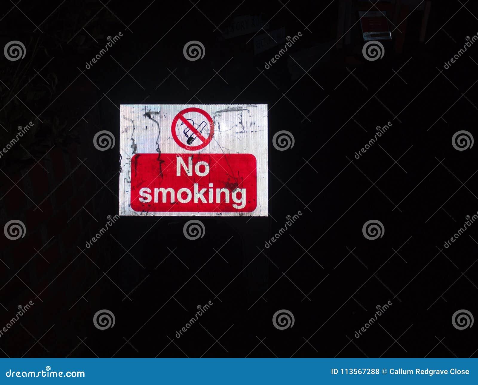 Vermelho da noite da construção do sinal de rua e branco não fumadores